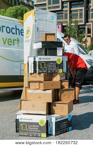 STRASBOURG; FRANCE - JUN 24; 2016: CHRONOPOST DPD and La Poste delivery parcel one above another in the city center with delivery van behind