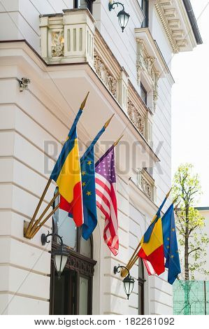 United State, European Union and Romanian flags above the building entrance of a Government building in Bucharest, Romania