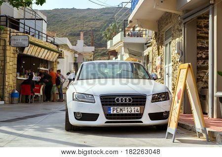 Bali Greece - April 30 2016: White sport-car Audi A5 coupe parked on Mithos beach promenade in sea bay of resort village Bali. Classic Greek stone architecture of resort tourists walk streets of city. Rethymno Crete Greece
