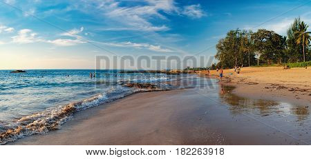 Khao Lak, Thailand - December 27, 2015: Beautiful seascape with sea and rolling waves in Nang Thong Beach. View of bright blue sea and crowded beach with bathing and walking people