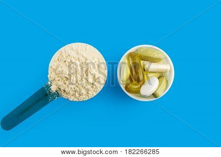 Protein powder in measuring plastic spoon and vitamin complex omega 3 glucosamine capsules supplements on blue background sports nutrition top view.