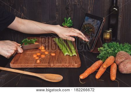 Woman Following Recipe On Tablet And Cooking Healthy Meal In The Kitchen, Cutting Vegetables On The