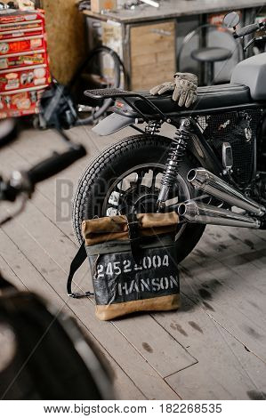 Leather backpack near the motorcycle. Half black motorcycle in the garage. Motorcycle kaferacers. Exclusive leather backpack. Backpack handcrafted.