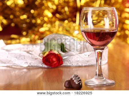 christmass dinner with rose candies and glass of red wine