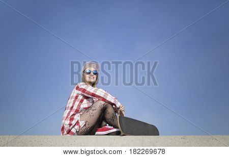 Smiling beautiful young woman posing with a skateboard against blue sky