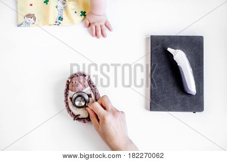 children's doctor work with stethoscope and hands on white desk background top view