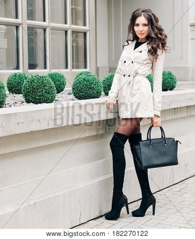 Long-legged brunette girl with long hair, dressed in a raincoat, high black high-heeled boots with a handbag posing near a boutique in the European city. Fashion and Style.
