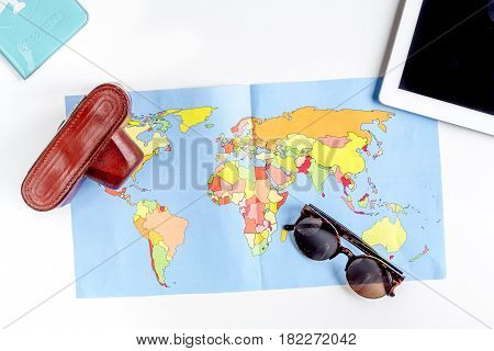 tourist lifestyle with camera, tablet and map on white table background top view