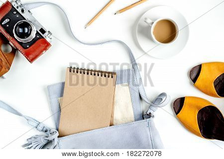 journey planning with tourist outfit and camera, cup of coffee on white table background top view