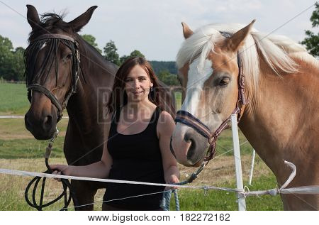 Young Woman Holding Two Horses
