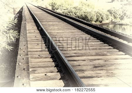 railroad tracks on a trestle crossing a river - travel concept, retro hand tinted opalotype processing