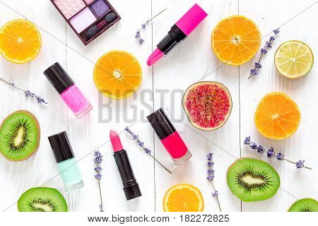 Citrus fruit pattern with kiwi, orange, lipstick and nailpolish on white wooden desk background top view