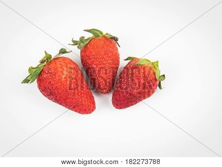 Fresh delicious red Strawberries isolated on white. Strawberries are with green stems and leaves