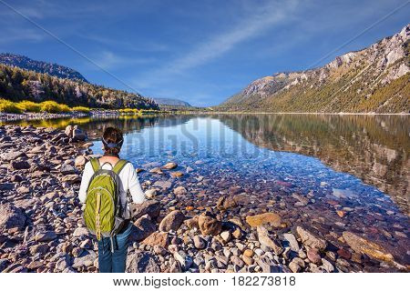 The elderly woman with tourist backpack admires lake and picturesque mountain in Bariloche. The concept of exotic and extreme tourism. Picturesque summer in Argentina