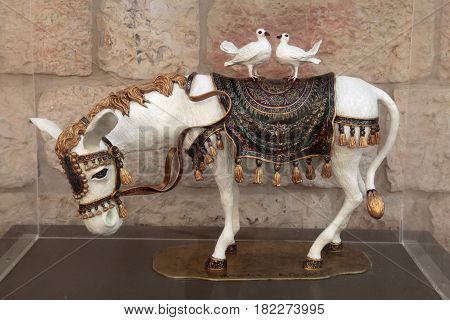JERUSALEM, ISRAEL - AUGUST 26, 2015: White donkey with pigeons statue in shopping mall open gallery, Jerusalem, Israel.