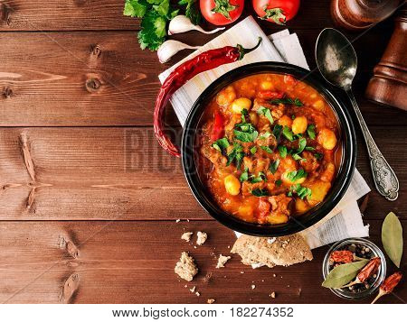 Goulash in ceramic bowl on wooden background. Traditional hungarian soup. Rustic style. Top view.