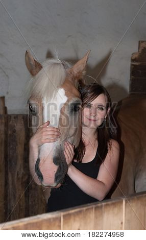 Young Woman Hugging Her Horse In Stable