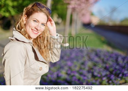 Young natural woman holding gasses in park at spring