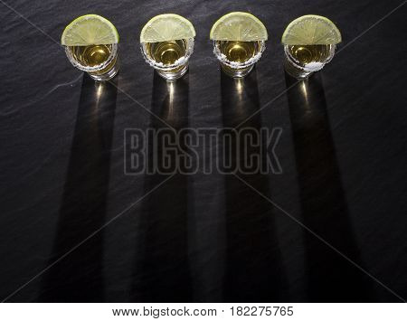 Tequila Shots With Deep Long Shadows On Black Background