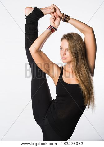 sports positive woman in sportswear standing one leg on the floor another stretched upwards, with positive emotions.