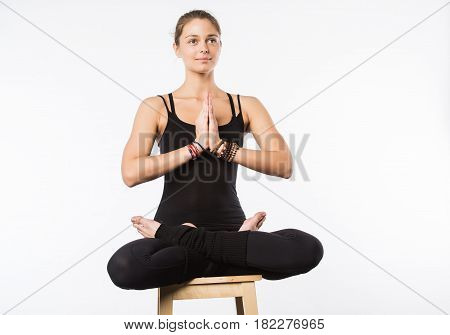 Sporty beautiful young woman sitting in Gomukhasana, Cowface pose, yin yoga Shoelace posture, asana for stretching hips and thighs, studio full length shot on white background, front view, isolated.