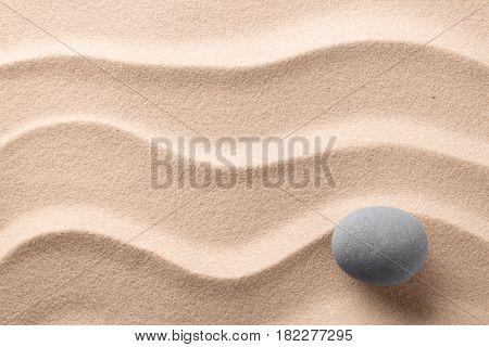 round stone on beach sand. Zen meditation rock.