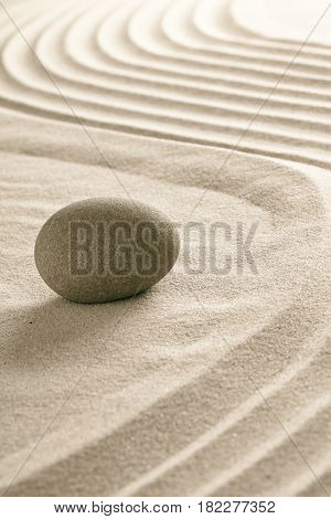 stone on raked sand in Japanese zen garden.