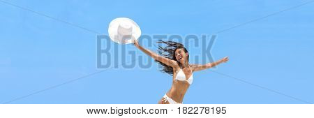 Happy carefree vacation woman jumping of joy and freedom in the air with sun hat on summer beach. Blue sky banner background. Happiness travel holidays healthy lifestyle concept.