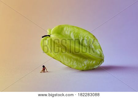Microworld with woman figure under the carambola tropical fruit on green pink background. Cartoon style food photography