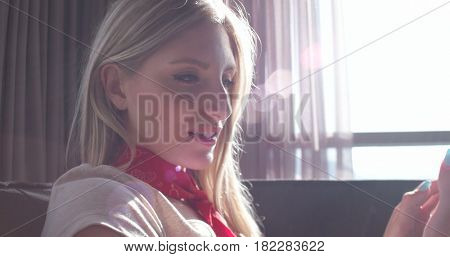 Blonde Woman Sitting On A Sofa Using Her Tablet