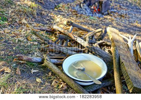 a bowl of hot fish soup standing amongst dry wood