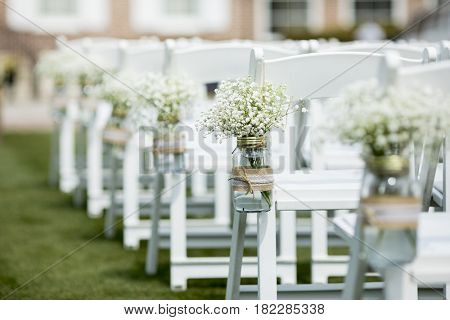 Jar with flowers hanging from chair for wedding