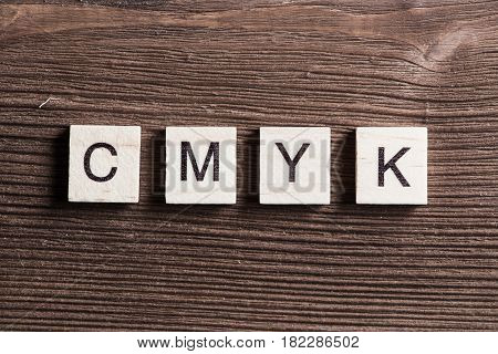Word cmyk collected of wooden elements with the letters