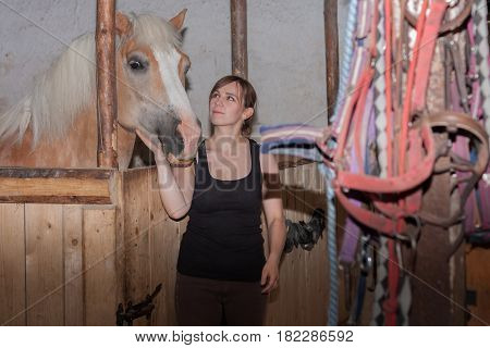 Young Woman Stroking Her Horse In Stable.