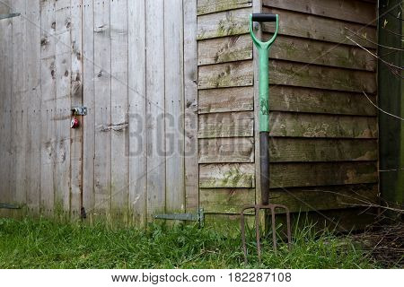 Old garden shed with old rusting garden fork