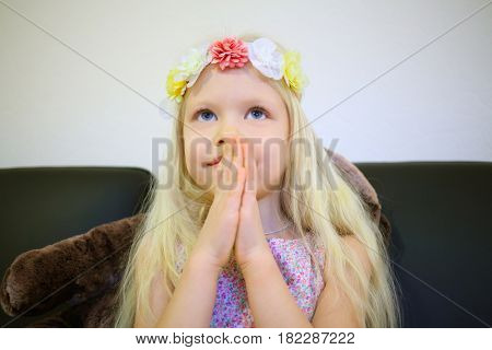 Little blonde girl in wreath, sits with clasped hands, smiles and looks up in room