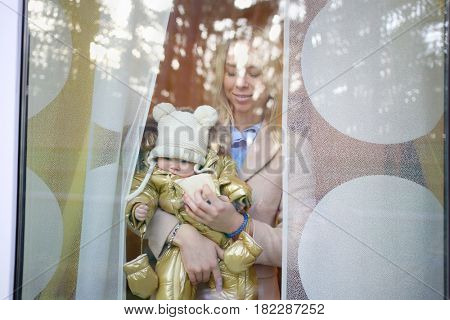 Happy mother holds baby in warm clothes behind window glass in house