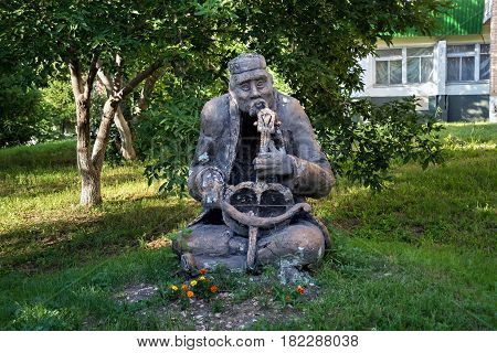 PETROPAVL, KAZAKHSTAN - JULY 24, 2015: Shabby sculpture of an old musician with a Kazakh national musical instrument in his hands. Petropavl is a city near border with Russia.