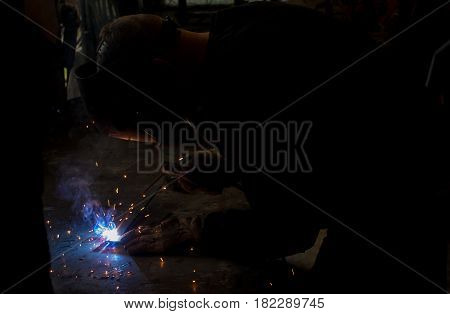 Skilled worksman welding wrought iron metal rods together in dark workshop with blue smoke and orange sparks wearing protective UV eyewear gear for eye protection