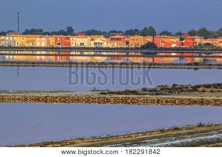 Colorful houses reflecting in water at Salin de Giraud, Camargue, France
