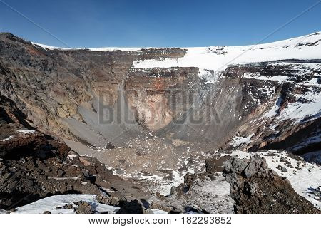 Volcanic landscape of Kamchatka Peninsula: view of large summit crater of active Tolbachik Volcano with steep sides and glaciers. Russian Far East Kamchatka Region Klyuchevskaya Group of Volcanoes.