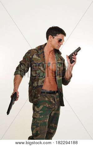 The handsome army man is holding pistols