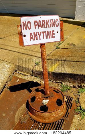 An old rusty car rim serves as a base for a No Parking sign in front of a garage.