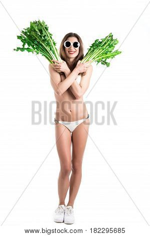 Portrait of young healthy woman in white bikini and white sunglasses with fresh chicory in a hand. Funny Vegetables Concept. Isolated on white