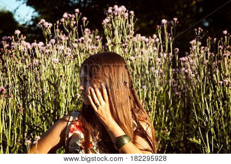 Young worried girl in the woods feeling anxious and scared. Beautiful Caucasian woman on a meadow among wildflowers nervously gesturing and looking aside