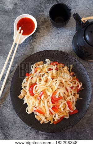 Asian cuisine: rice noodles with fried pork and bell pepper. Top view