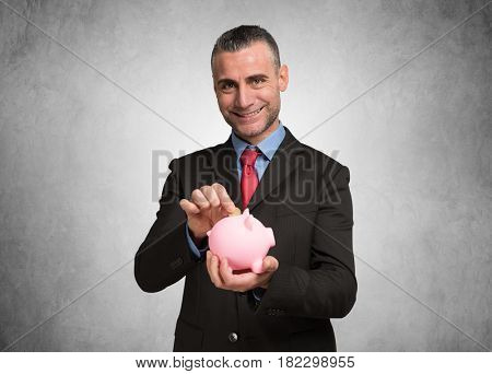Smiling man putting a coin in a piggy bank