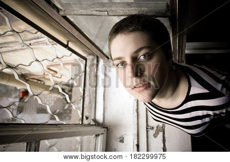 A Young Girl With A Short Hair Stays By The Window And Looks Up At The Camera