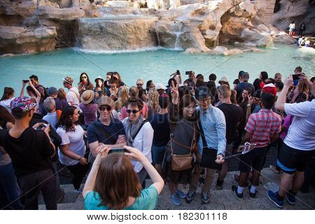 ROME, ITALY - APRIL 10, 2017: Crowd of tourists visiting and posing in the front of the Trevi fountain (Fontana di Trevi), one of the major sights of Rome