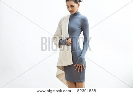 Cute girl is posing in the studio on the light background. She wears a gray dress and a white coat. Woman holds left hand on the hip, right hand next to her belly and looks downward. Horizontal.
